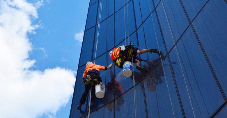 dois alpinistas industriais içados em uma fachada de vidro executando a limpeza de prédios