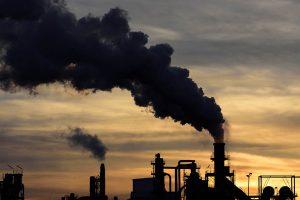 A falta de políticas de controle, uso de tecnologias obsoletas e lixiviação dos recursos estão entre as principais causas da poluição industrial. Na imagem é possível ver a fumaça negra saindo de uma fabrica.