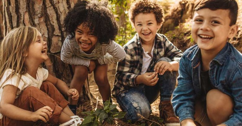 Quatro crianças se divertindo na natureza. Veja como crianças e meio ambiente se integram!