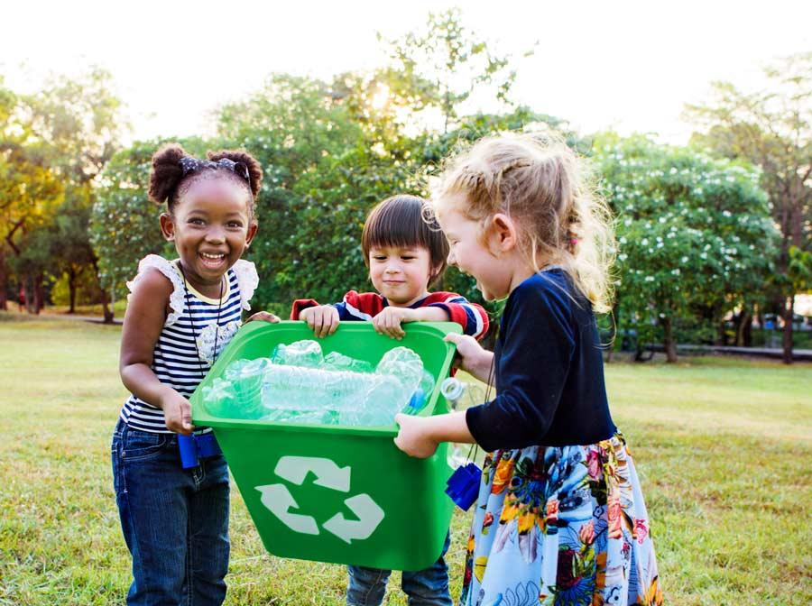 Três crianças cuidando de reciclagem. Entenda como crianças e meio ambiente se ajudam!