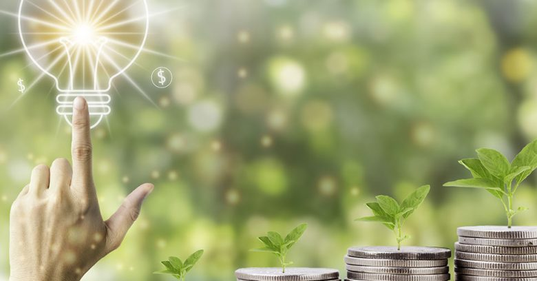 imagem representativa de uma lâmpada e moedas com a natureza ao fundo traz a analogia de economia de energia na empresa