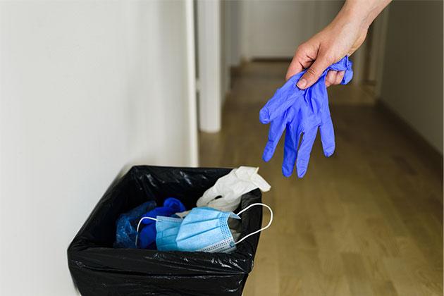 pessoa jogando a luva no lixo descartável correto exemplifica a sustentabilidade na área da saúde
