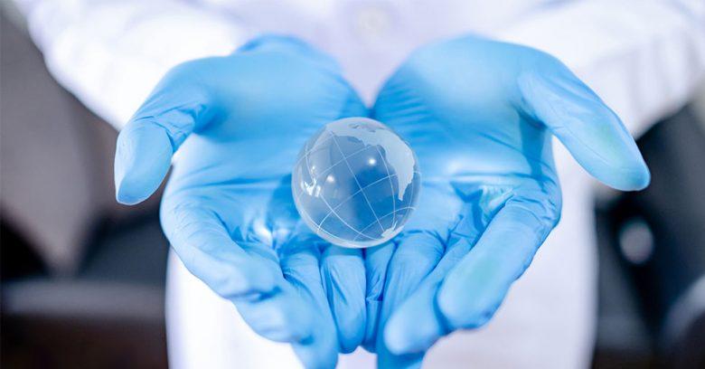 profissional com luva azul segurando um globo transparente representa a sustentabilidade na área da saúde